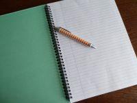 Foto von einer Kladde mit einem Kugelschreiber.